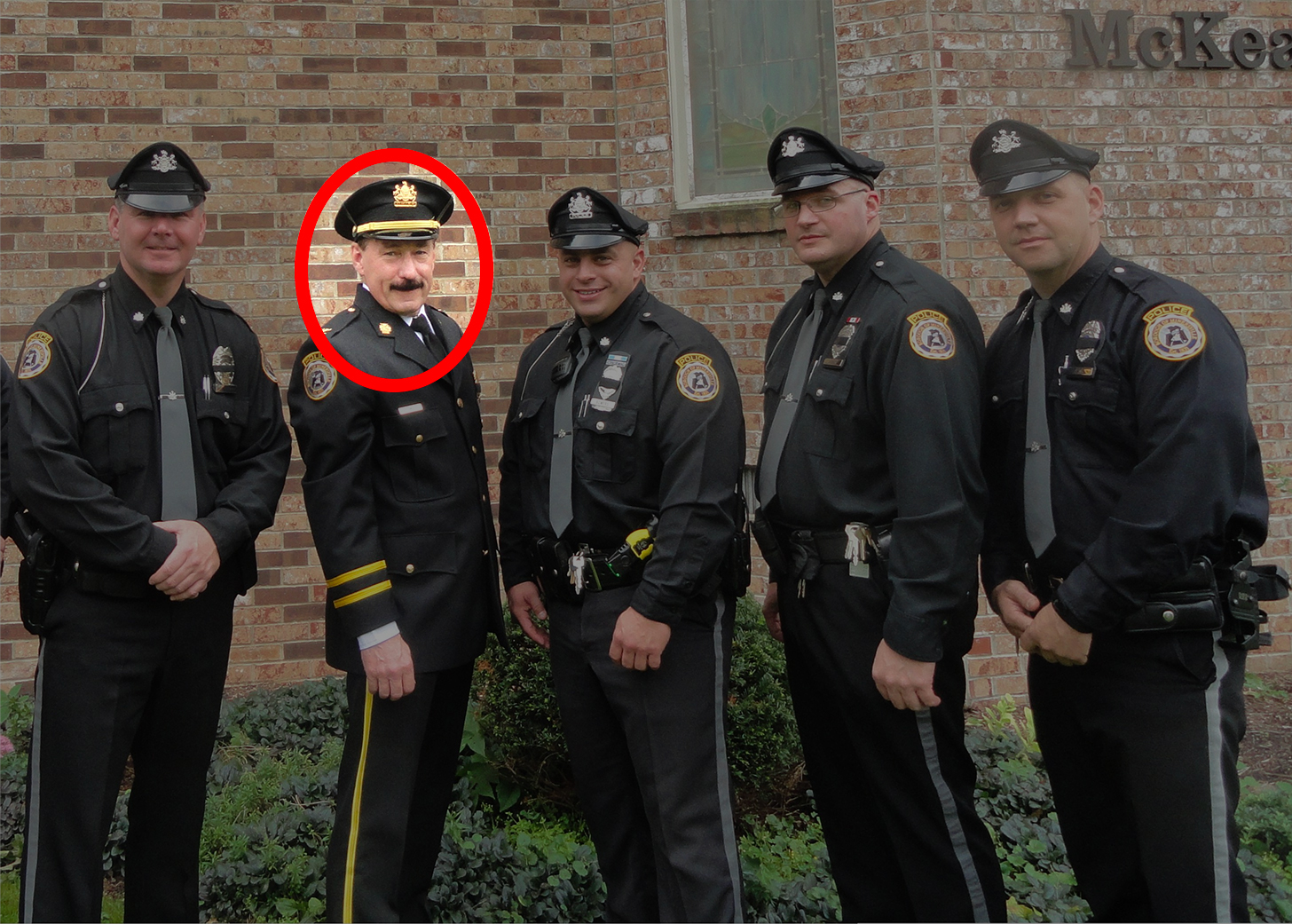 Image of 5 police officers from Minersville, Pennsylvania. They are posing for the camera. Highlighted in a red circle is Minersville Police Chief Michael Combs.